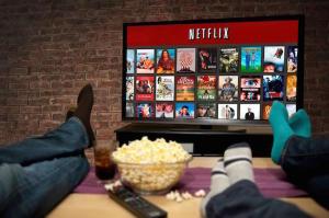 Persone sedute sul divano che guardano Netflix